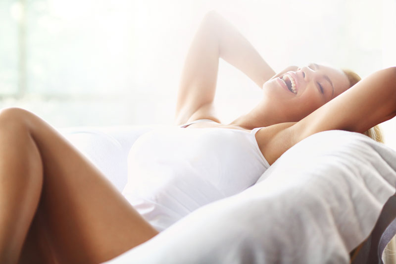 Elite+ | Woman relaxed, laying down smiling