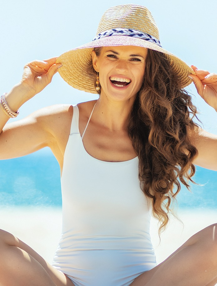 Woman sitting at beach with hat, smiling